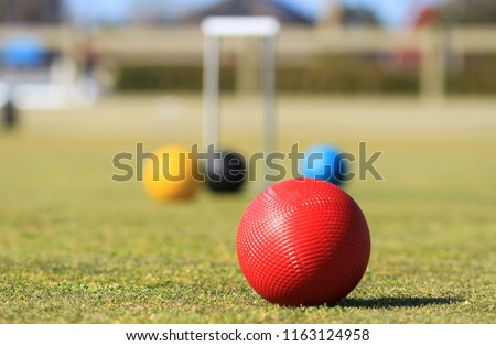 In the foreground is a red croquet ball on a green croquet lawn in Australia with a defocused croquet hoop and balls in the background