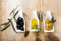 in the foreground, on the rustic wooden table, some white ceramic bowls with green and black olives and extra virgin olive oil.