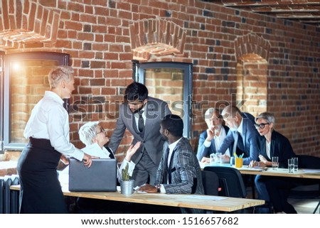 In the foreground two blonde caucasian women, caucasian bearded brunette man, african man discuss. On the background two blonde caucasian men and one woman at table discuss project. #1516657682