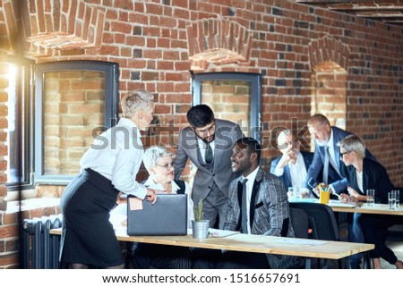 In the foreground two blonde caucasian women, caucasian bearded brunette man, african man talk. On the background two blonde caucasian men and one woman at table. #1516657691