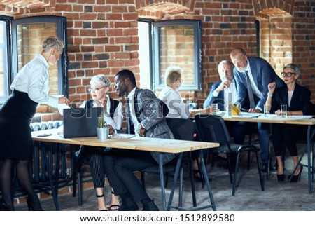 In the foreground two caucasian blond women and one african man work at table on laptop. On the background two caucasian blond men and two caucasian blond women work at table. #1512892580