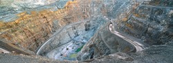 In the gold mine,  a large yellow truck carrying gold ore to the processing machine, panorama view