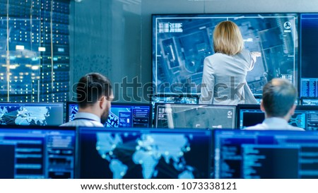 In the Government Surveillance Facility Team of Officers Organize Interception Plan with Help of Satellite Navigation. Big Screen Shows Top Down Images of the Target.