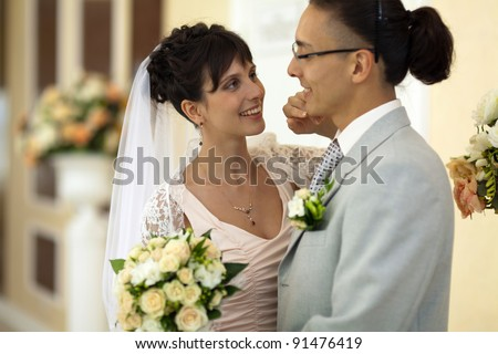 In the hall of the palace wedding the young bride and groom are passionate about each other and do not see anyone
