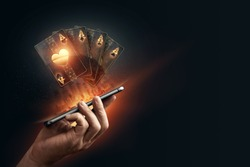 In the hands of a smartphone with playing cards, black-gold background. Concept of online gambling, online casino. Copy space