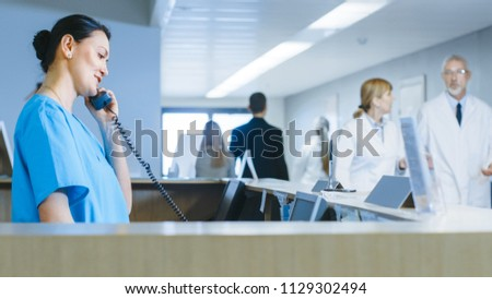 In the Hospital at the Reception Desk Nurse on Duty Talking on Phone. Busy Modern Hospital with Best Specialists and Medicare in Country.