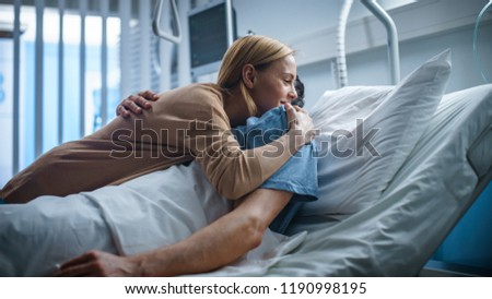 In the Hospital, Happy Wife Visits Her Recovering Husband who is Lying on the Bed. They Lovingly Embrace and Smile. #1190998195