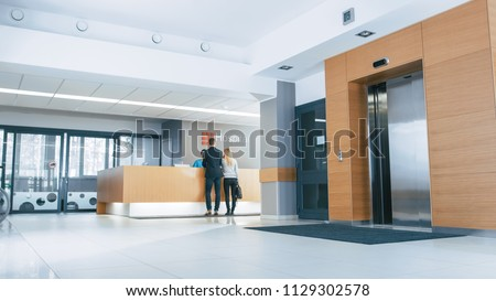 In the Hospital Lobby Young Couple Patients Talks to Receptionist. New, Modern Medical Facility.