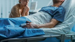 In the Hospital Sick Man Lying on the Bed, His Visiting Wife Hopefully Sits Beside Him and Prays for His Rapid Recovery. Tragic, Somber and Melancholy Scene.