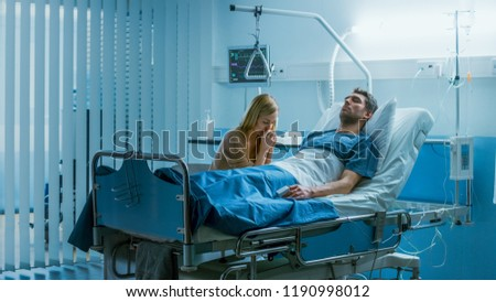 In the Hospital Sick Man Lying on the Bed, His Visiting Wife Sorrowfully Sits Beside Him and Prays for His Rapid Recovery. Blue and Melancholy Color of the Scene.