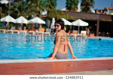 In the hot afternoon the woman has a rest near azure pool