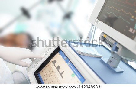 In the ICU. Doctor changes the parameters artificial lung ventilation near the bedside.