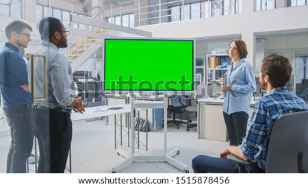 In the In Industrial Design Facility Team of Engineers and Technicians have a Meeting, Female Specialist Leads Briefing, Talks and Use Digital Interactive Whiteboard with Green Mock-up Screen