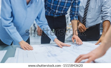 In the Industrial Engineering Facility: Diverse Group of Engineers and Technicians on a Meeting Gather Around Table Unravel Sheets of Engine Design Technical Drafts, Have Discussion, Analyse Drawings