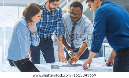 In the Industrial Engineering Facility: Diverse Group of Engineers, Technicians, and Specialists on a Meeting, Have Discussion, Analyse Engine Design Technical Drafts that are Lying on the Table
