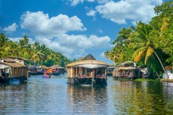 In the Kerala Backwaters of southern India, covered barges travel along a narrow canal lined with coconut palm trees, part of a large network of interconnected inland waterways.