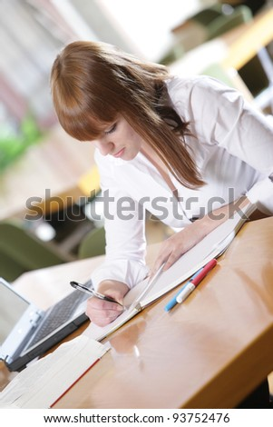 in the library -young female student with laptop and books working in a high school library - stock photo