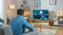 In the Living Room Man Sitting on a Couch Holds Controller Playing in a Console Video Game, 3D Action Shooter Gameplay Shown on TV Screen.