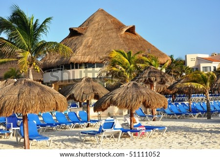 In the Mexican style. A resort building with a grassy roof on seacoast. Dark blue plank beds, sand, the umbrellas protecting from the sun.