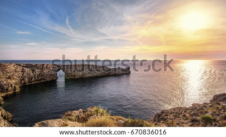 In the middle of the Mediterranean we see the beautiful arch of natural rock, Pont d en Gil in Menorca Spain. The combination of sea, rocks and sky creates an atmosphere that leaves us perplexed. - Shutterstock ID 670836016