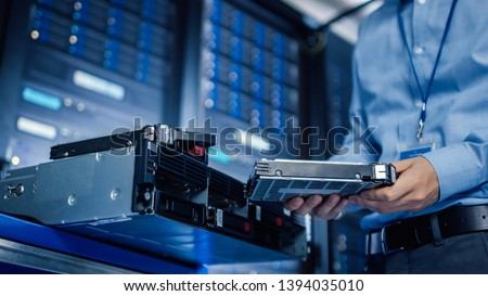 In the Modern Data Center: IT Engineer is Holding New HDD Hard Drive Prepared for Installing Hardware Equipment into Server Rack. IT Specialist Doing Maintenance and Updating Hardware. Foto stock ©