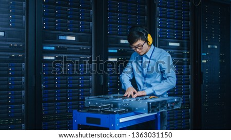 In the Modern Data Center: IT Technician Wearing Protective Headphones Working with Server Racks, on a Pushcart Installing New Hardware. Engineer Doing Maintenance and Diagnostics of the Database.