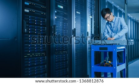 In the Modern Data Center: IT Technician Working with Server Racks, on a Pushcart Installing New Hardware. Engineer Doing Maintenance and Diagnostics of the Database.