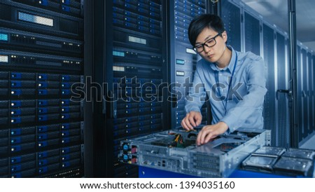 In the Modern Data Center: IT Technician Working with Server Racks, on a Pushcart Various Equipment Needed for Installing New Hard Drives, Doing Hardware Maintenance and Diagnostics.