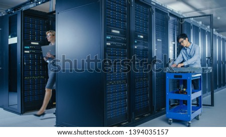 In the Modern Data Center: Team of IT Technicians Working with Server Racks, Man with Pushcart Changes Faulty Hard Drives, Doing Hardware Maintenance and Diagnostics.
