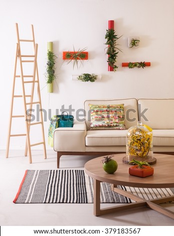 In the modern living room with comfortable sofas, natural wood staircase, flowering of modern wall decor
