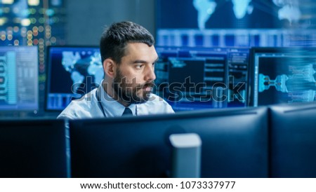 In the Monitoring Room Technical Operator Attentively Monitors Stability of the System. He's Surrounded By Screens Showing Technical Data. #1073337977