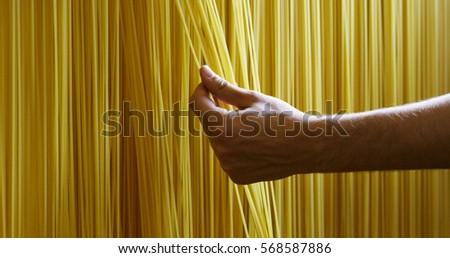 Stock Photo in the morning a young boy touches the hand of a fresh pasta to dry put them to ensure a high quality