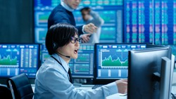 In the Network Operations Senior Trader Dictates Stock Numbers to Their Operator who Makes Call with a Headset. In the Background Traders Discuss Data Shown on Monitors.