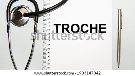 In the notebook is the text troche, next to the stethoscope and the pen. Zdjęcia stock ©