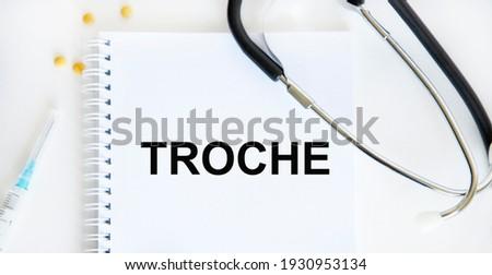 In the notebook text TROCHE, next stethoscope, syringe, tablets. Zdjęcia stock ©