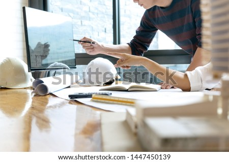 in the office  engineer or architectural project, two engineering or architecture discussing and working on blueprint with architect equipment, Construction concept.