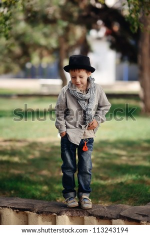 in the park on a stone fence is a boy in jeans and a hat