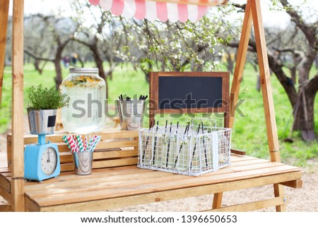In the park on the green lawn a wooden counter with a lemonade. An adorable summer lemonade stand. Cooking homemade lemonade in the garden. Lemonade in a glass jar on a wooden stand in the open air