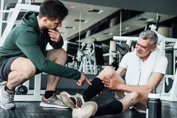 In the photo, two people in the gym, one of them on the floor with an injured leg, a rehabilitation coach helps him.