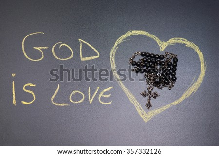"In the picture a rosary iron at the center of a heart drawn on the left side the word ""god is love"" with a crayon"