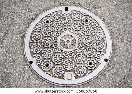 In the picture we can see a circular design of a classic art on a manhole cover. The art looks very neat and clean. It is made of steel and concrete.
