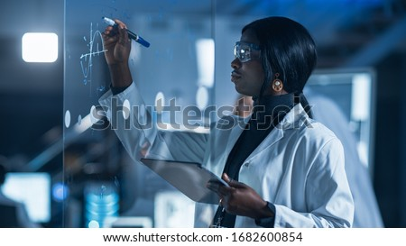 In the Research Laboratory Smart and Beautiful African American Female Scientist Wearing White Coat and Protective Glasses Writes Formula on Glass Whiteboard, References Her Tablet Computer