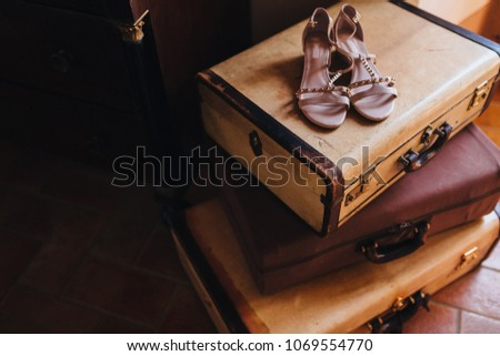 in the room on the floor old suitcases are stacked, on top are women's shoes