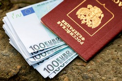 In the russian passport lies a pack of euros lying on the street. Inscription in Russian passport of the Russian Federation