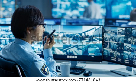 In the Security Control Room Officer Monitors Multiple Screens for Suspicious Activities, He Reports any Unauthorised Activities in His Walkie-Talkie. He's Surrounded by Monitors. #771481843