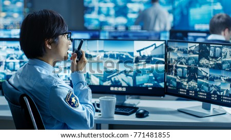 In the Security Control Room Officer Monitors Multiple Screens for Suspicious Activities, He Reports any Unauthorised Activities in His Walkie-Talkie. Сток-фото ©