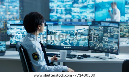In the Security Control Room Officer Monitors Multiple Screens for Suspicious Activities, He Drinks from a Mug. He's Surrounded by Monitors and Guards Port of National Importance. #771480580