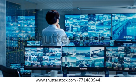In the Security Control Room Officer Monitors Multiple Screens for Suspicious Activities. He Guards Internationally Important Logistics Facility. Сток-фото ©