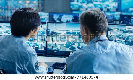 In the Security Control Room Two Officers Monitoring Multiple Screens for Suspicious Activities, They Report any Unauthorised Activities with Walkie-Talkie. They  Guard Object of National Importance.