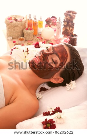 in the spa salon a beautiful girl doing a chocolate mask on your face - stock photo